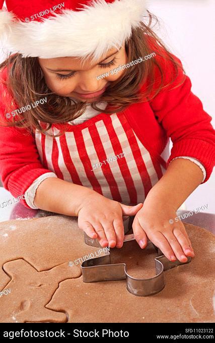 Little girl cutting out gingerbread men
