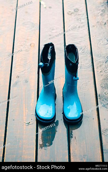 Blue wellies standing on a wooden porch while raining
