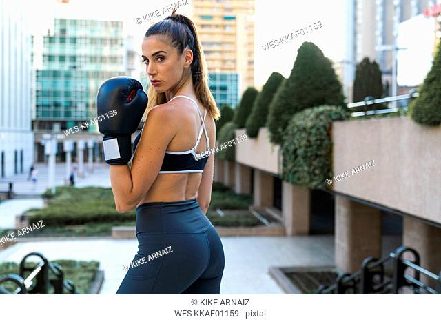 Portrait of sportive young woman wearing boxing gloves in the city