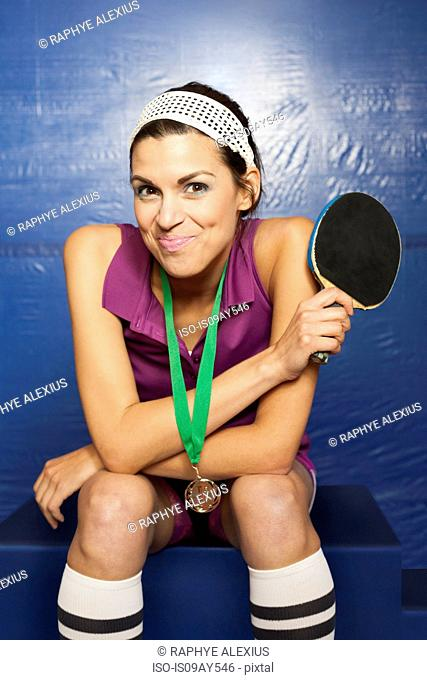 Table tennis medalist holding up bat