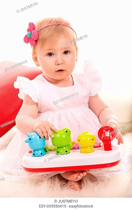 Beauty baby girl eight months age playing with colorful toys with animals