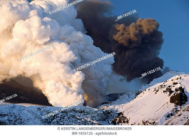 Cloud of ash from Eyjafjallajoekull volcano and a steam plume from the lava flow in Gigjoekull glacier tongue, Iceland, Europe