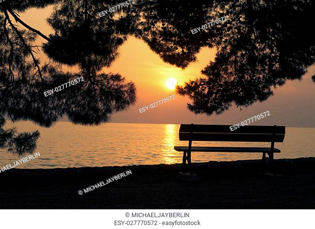 Nobody sitting on an bench at the Mediterrean Sea in Croatia at sunset