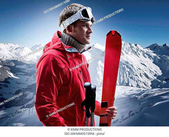Man carrying skis on snowy mountain