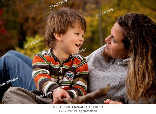 Smiling mother, in her 30s, holding her three year old smiling son and holding her gaze with a loving look while reclining in their backyard in the fall with...