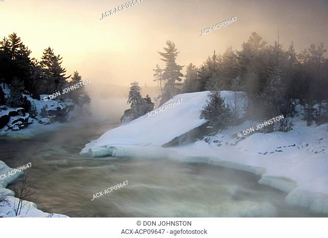 Tree silhouettes and rising mists near rapids of Wahnapitei River at sunrise, Wanup, Ontario, Canada