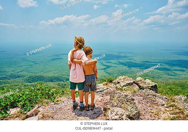 Boys on mountain peak looking away at view, Aguas Calientes, Chuquisaca, Bolivia, South America