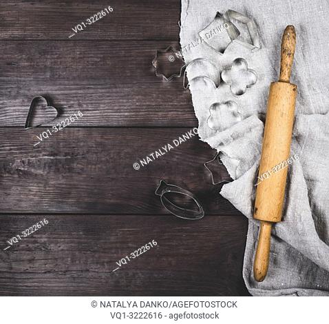 wooden rolling pin and iron bakeware on a brown wooden table, copy space
