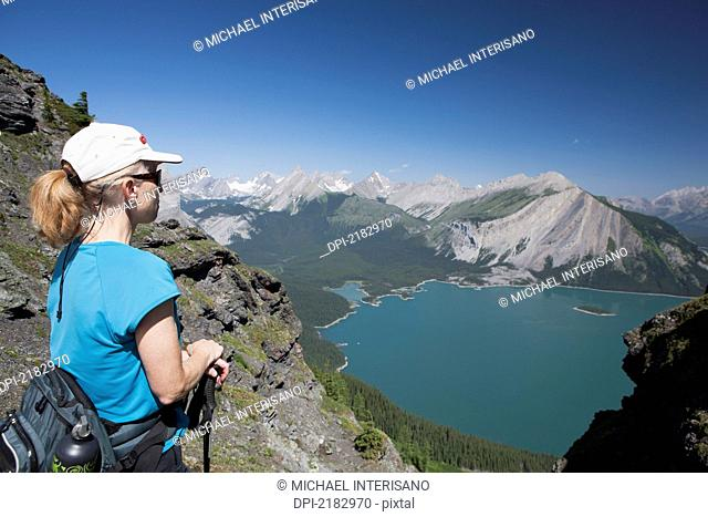 Female Hiker On A Mountain Ridge Overlooking An Emerald Lake And Mountains Below With Blue Sky In Kananaskis Provincial Park, Alberta Canada