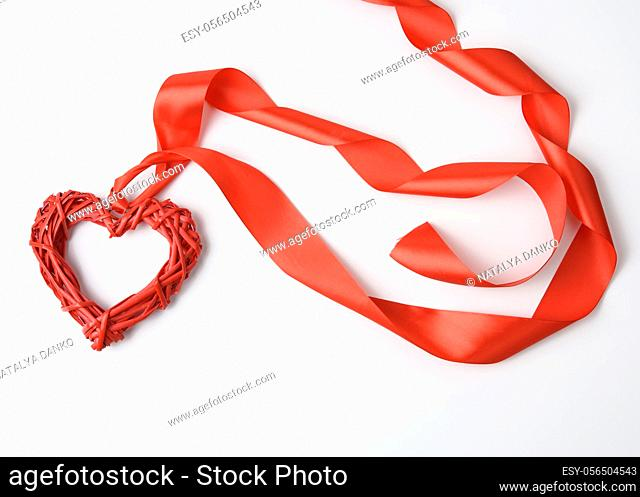red braided heart and twisted silk ribbon on white background, top view