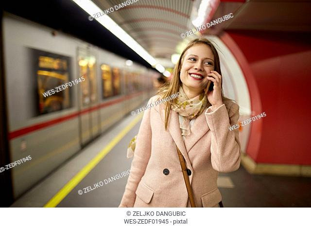Austria, Vienna, portrait of smiling young woman on the phone at underground station platform