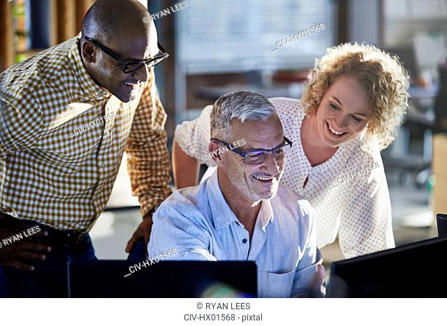 Smiling business people working at computer in office