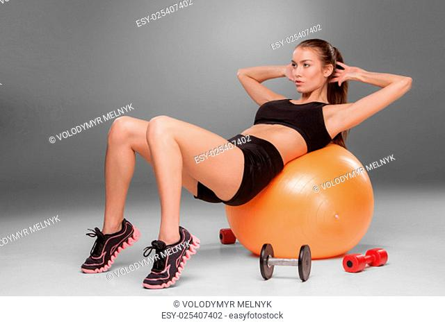 Sporty woman doing aerobic exercise on a fitness ball on grey background