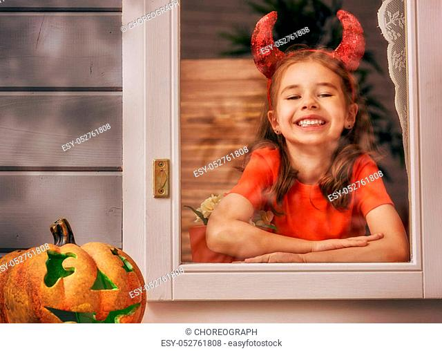 Happy Halloween! Cute cheerful kid looking on the window. Beautiful child girl in devil costume in the house decorated to Halloween