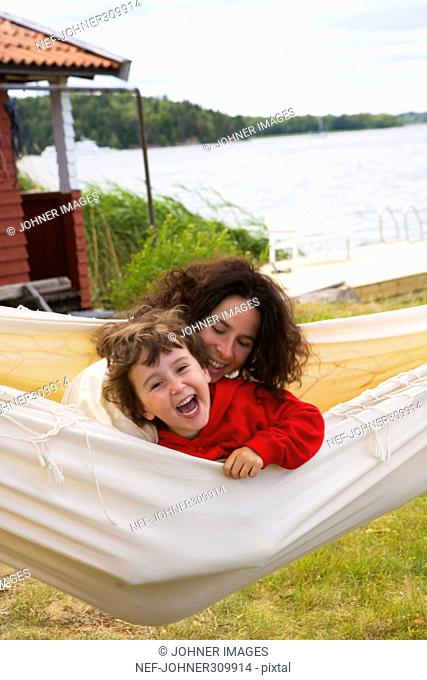 Mother and daugther playing in a hammock