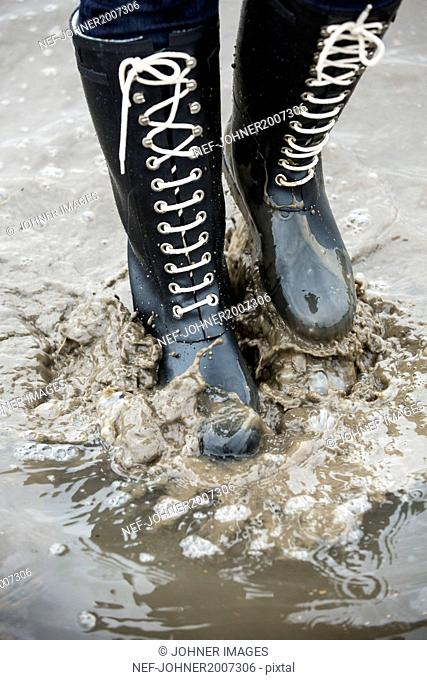 Person in wellington splashing mud, low section