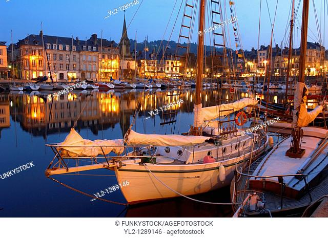 Night harbour scene with yachts and restaurant lights. Honfleur, Normandy, France