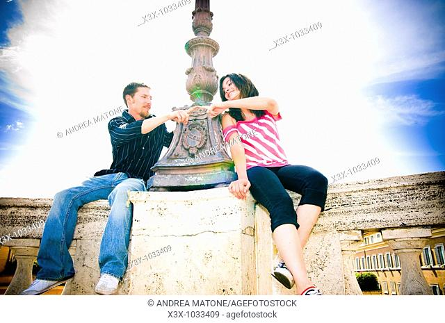 Young couple sitting near lamp post touching fingers together, Rome, Italy