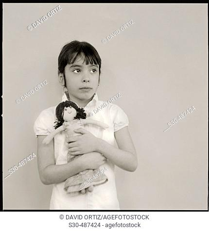 Seven year old girl with far away look in her eyes clutching a rag doll