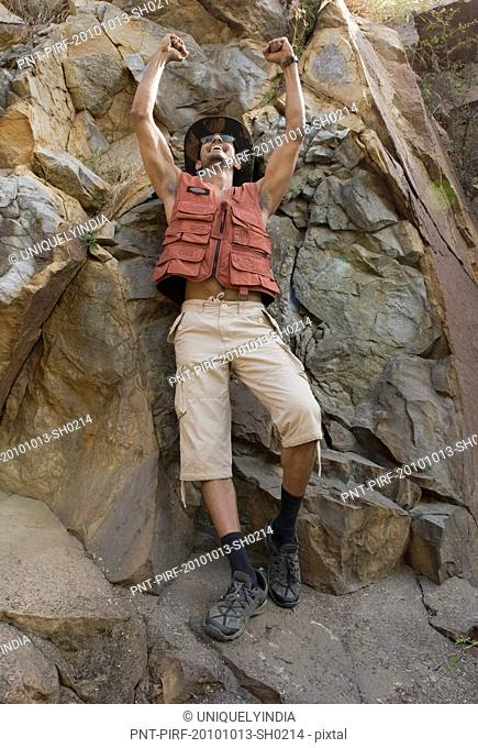 Hiker on rocks with his arms raised