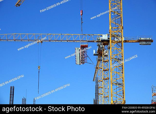 31 July 2020, Berlin: During construction work, construction cranes stand on the site of the former central cattle and slaughterhouse in Prenzlauer Berg