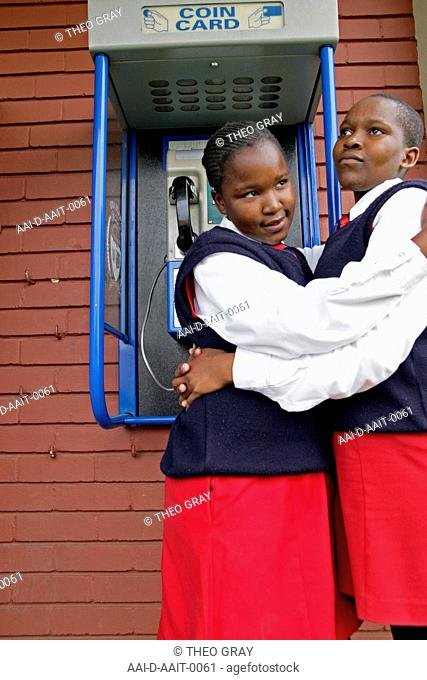 School girls hugging by payphone, St Mark's School, Mbabane, Hhohho, Kingdom of Swaziland