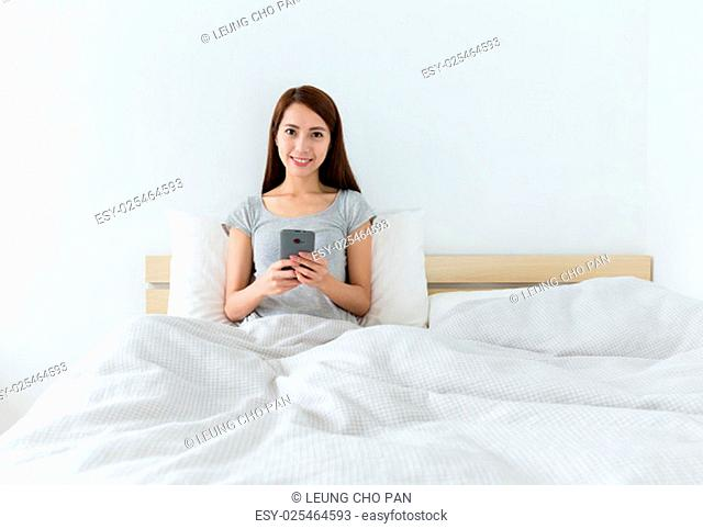 Asian young woman using cellphone on bed