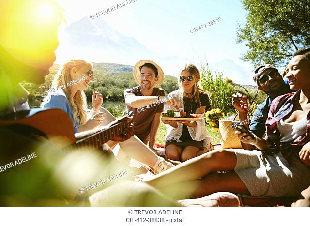 Young friends hanging out, enjoying picnic in sunny summer park
