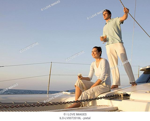 A couple relaxing with a drink on a boat
