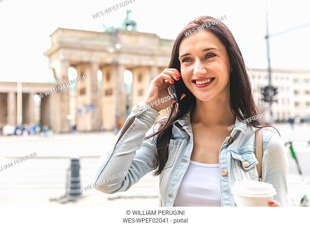 Happy young woman on the phone at Brandenburg Gate, Berlin, Germany