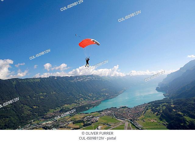 Male sky diver with parachute over lake, Interlaken, Berne, Switzerland