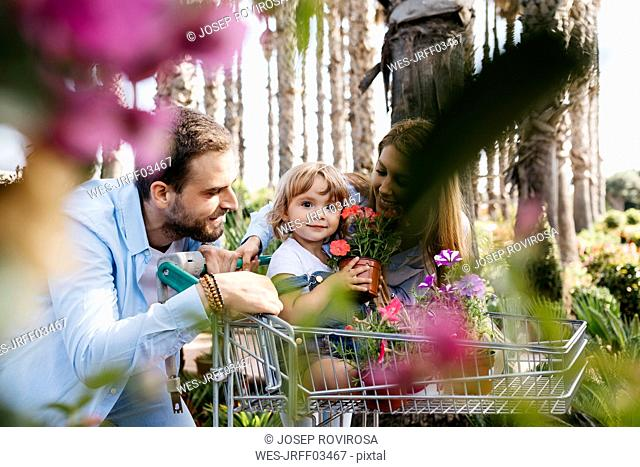 Family buying plants in a garden center wth the daughter in shopping cart holding a flower