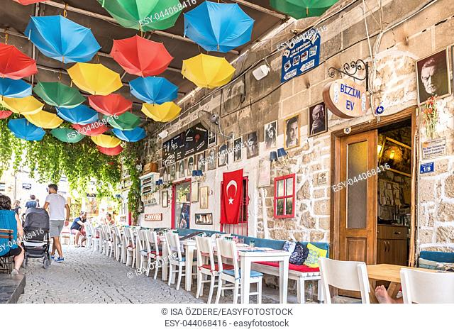 Unidentified People walk at a street with cafe and restaurant with tables and chairs around at Alacati Town, a popular destination for traveling and vacation in...