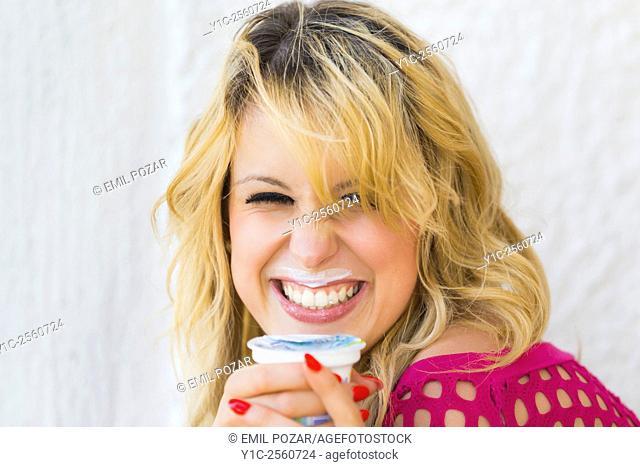 Eating yogurt messy lips smiling woman portrait
