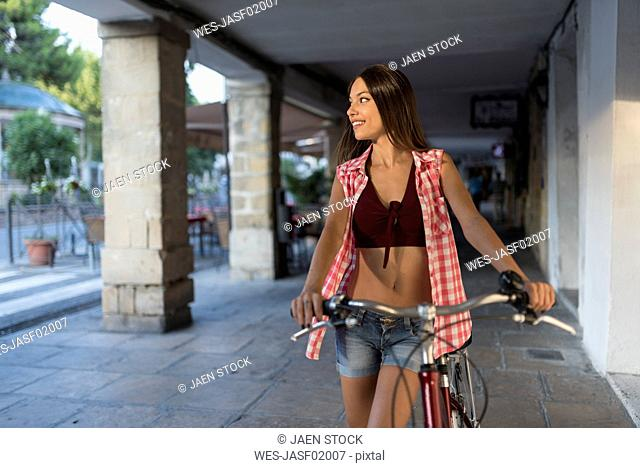 Spain, Baeza, smiling young woman with bicycle