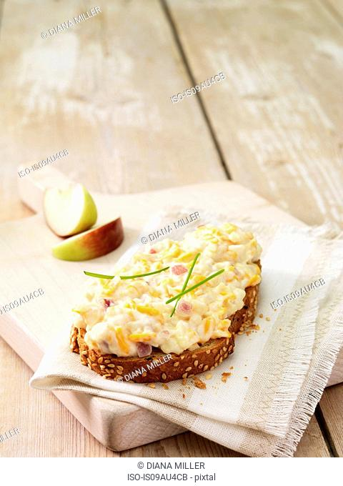 High angle view of grated cheese and red onion on wholemeal bread with apple wedges