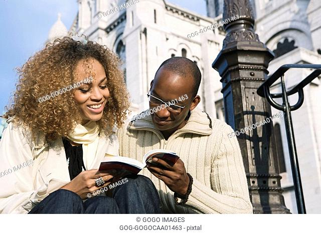 African couple looking at guidebook
