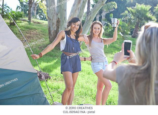Three young female friends taking photographs on smartphone