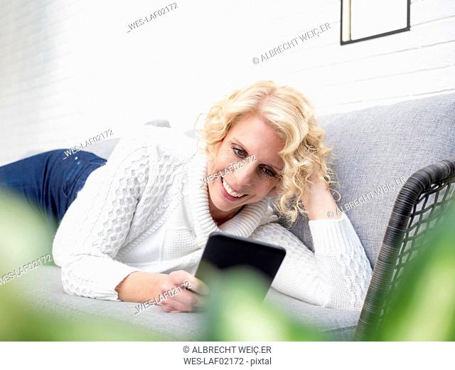Smiling mature woman lying on couch at home reading e book