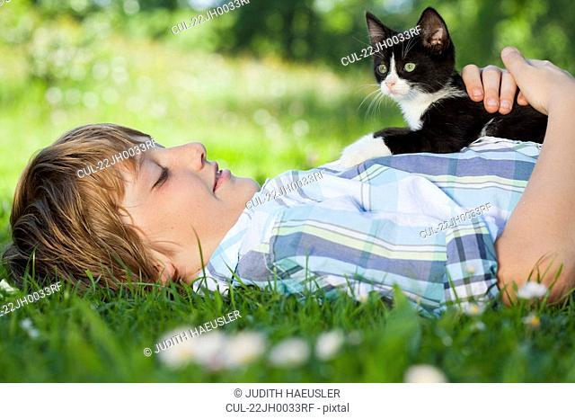 Boy in meadow hugging a cat