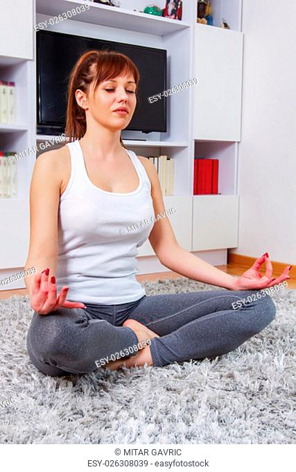 Fit Young Woman Relax at home. Yoga Meditation.Caucasian female relaxing at home. Healthy Lifestyle