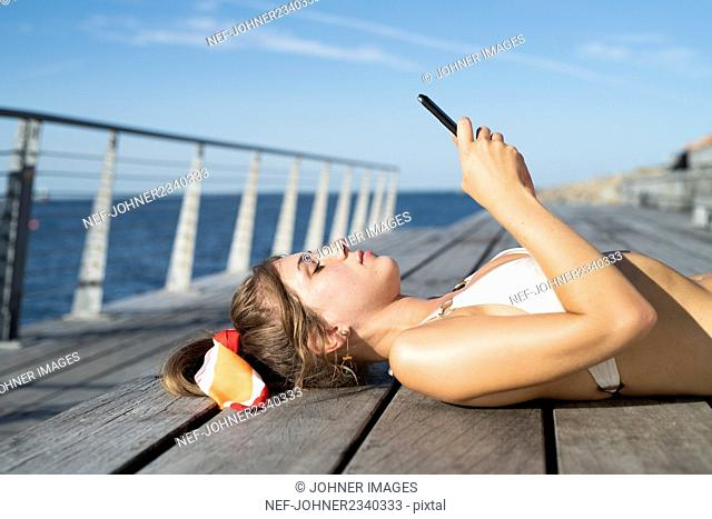 Young woman lying on pier and holding cell phone