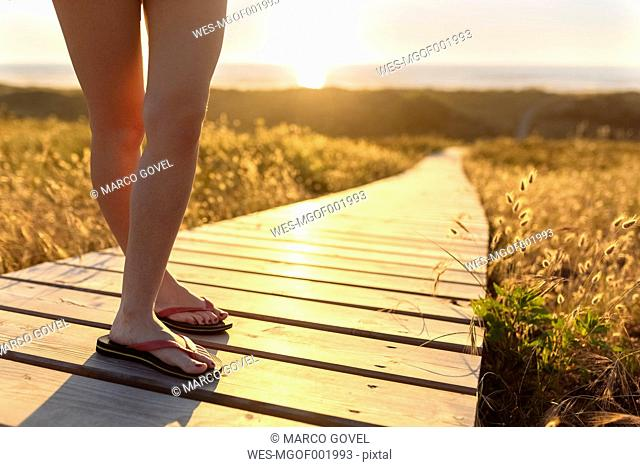 Legs of young woman standing on boardwalk at the beach