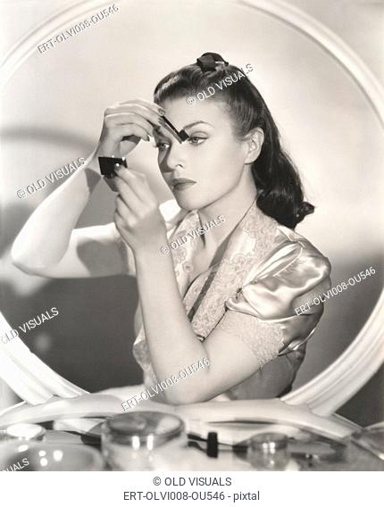 Reflection of woman in mirror applying eye make-up