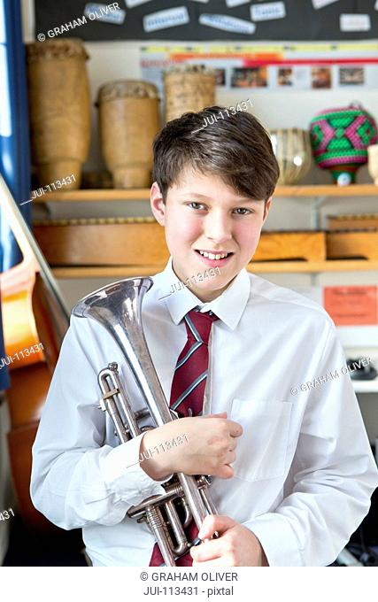 Portrait confident middle school student with trumpet in music classroom