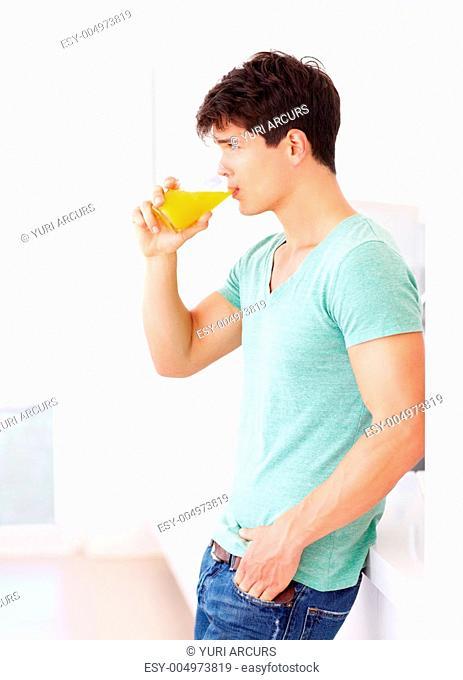 Healthy young guy drinking orange juice - profile