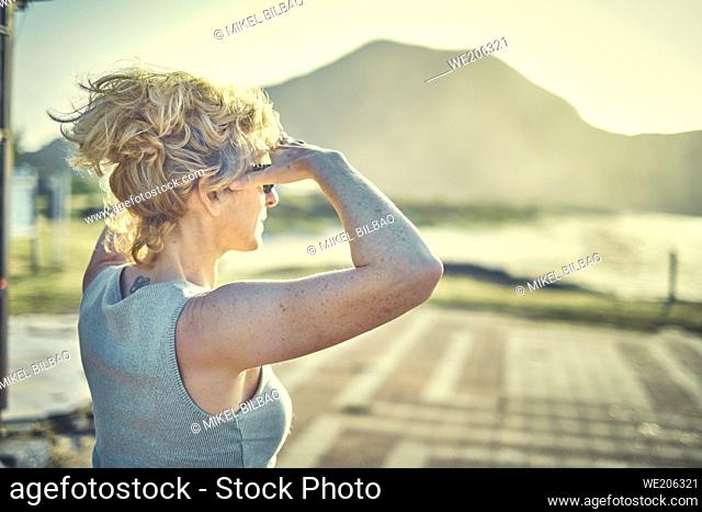 Back view of a young blonde caucasian woman with a tatoo in is nape outdoor in a beach area in a sunny day. Berria beach, Cantabria, Spain, Europe