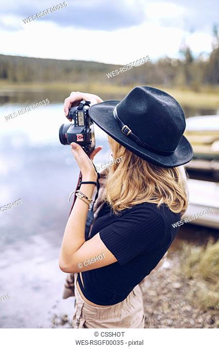 Sweden, Lapland, young woman wearing black hat taking photo with camera