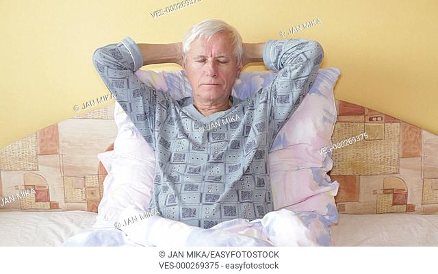 Sick senior man in bed with sore throat