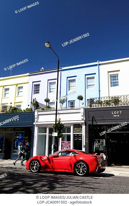 A red Ferrari parked outside boutique shops on Westbourne Grove in Notting Hill